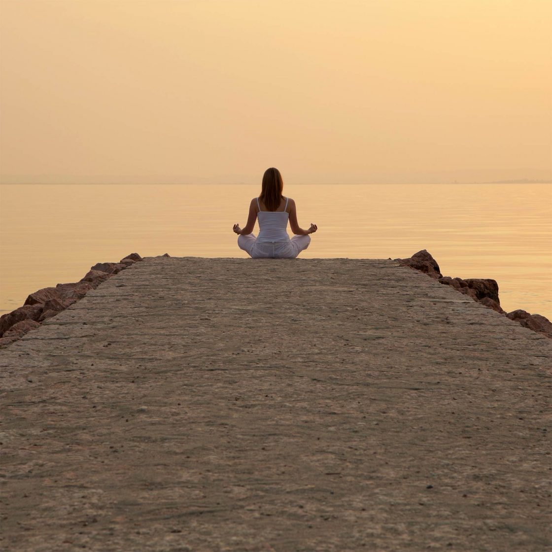 Girl practising meditation by the sea