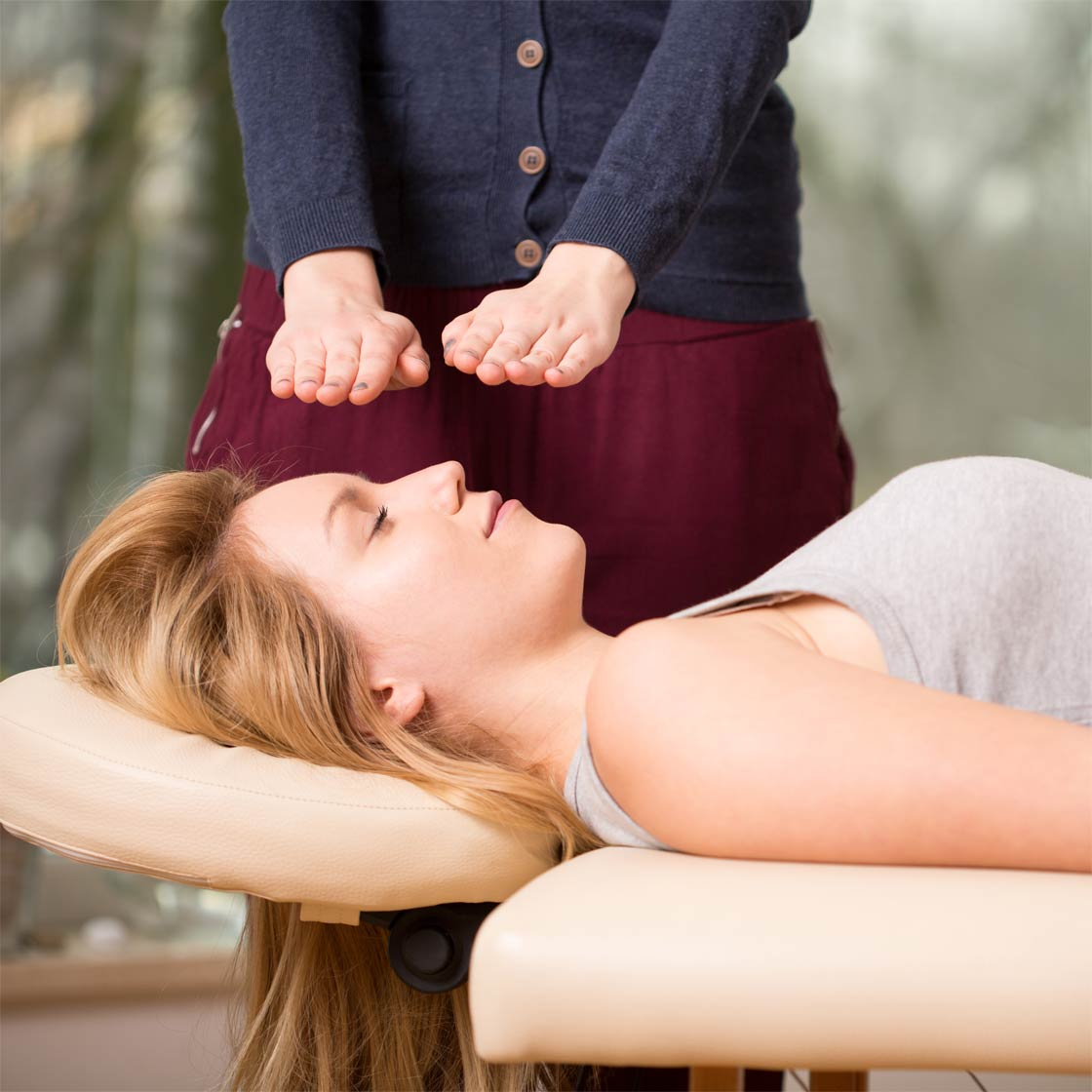Young woman receiving hands-off Reiki treatment