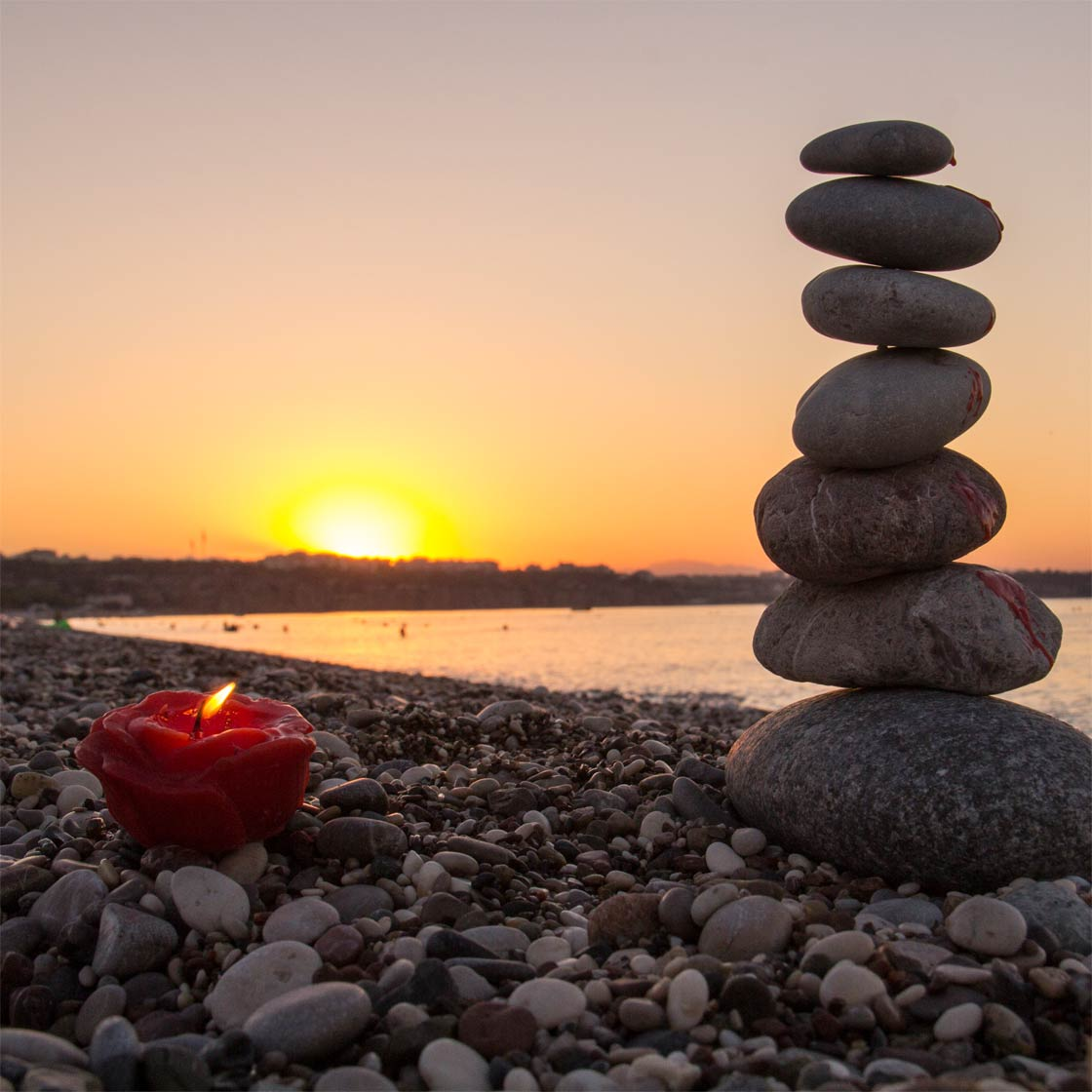 Standing stones with candle on beach
